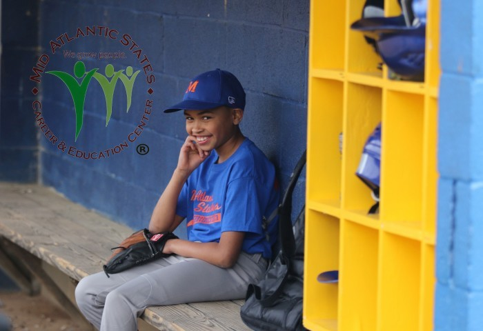 Little League player smiling at camera while sitting in the dugout