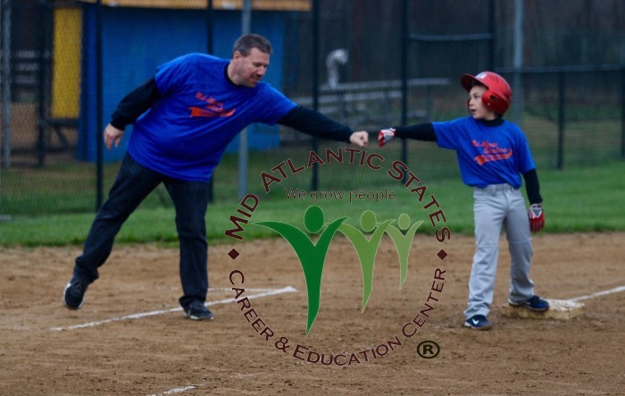 Little League coach and player fist bumping