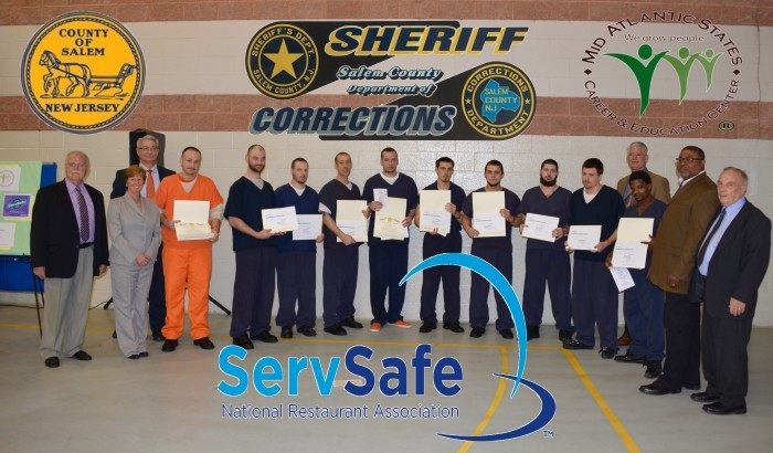 Freeholders standing with inmates who are holding their certificates
