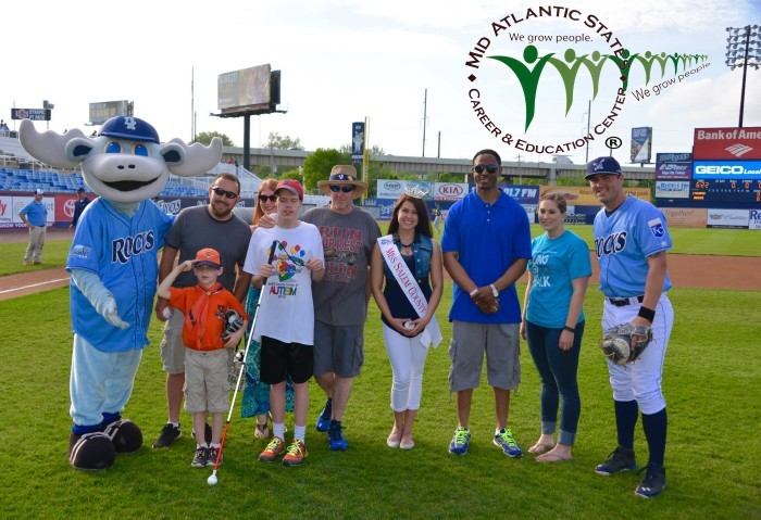 Group of adults and kids on baseball field with a player and mascot