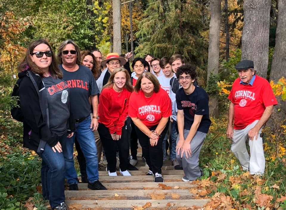 Students wearing Cornell t-shirts standing on steps in the woods
