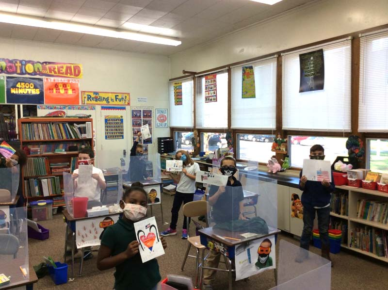 Grade school class show their hand drawn pictures