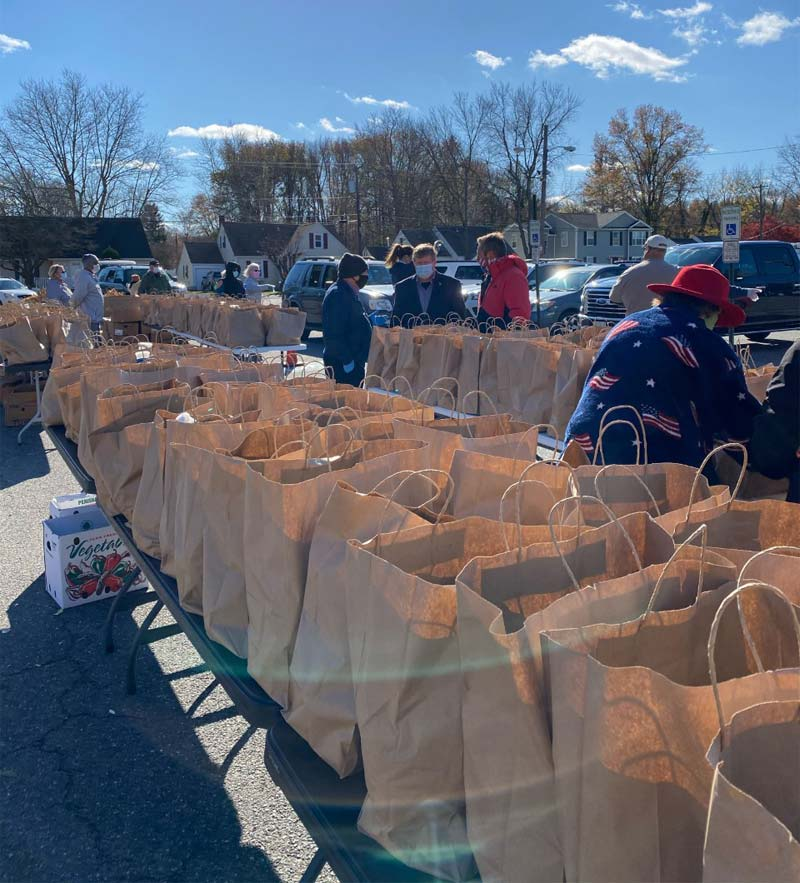 Table filled with bags to put food in with volunteers in background