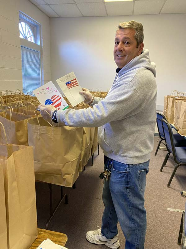 Mid Atlantic employee Jeff Truax putting cards into food bags